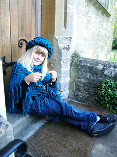 Beth_poncho_sitting_down_by_door_with_daisy_chain_small2