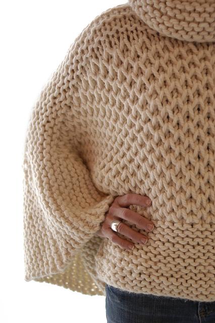 Болеро цвета бирюзы связано спицами из толстой пряжи узором из кос.